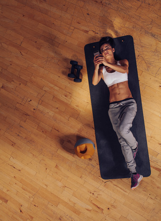 women sport: Overhead view of fitness woman lying on mat using mobile phone. Top view of young female taking break from exercise.