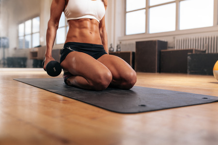 Cropped image of muscular woman exercising with dumbbells while sitting on fitness mat in gym. Focus on abs.