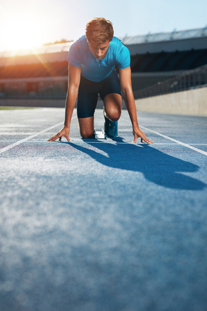 athlete: Professional male track athlete in set position on sprinting blocks of an athletics running track in stadium. Stock Photo