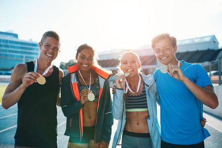 メダルを見せて恍惚とした若いランナーの肖像画。若い男性と女性は、レースを実行する勝者後興奮してください。スタジアムで選手の多民族のチ 写真素材