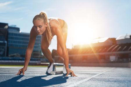 ランニング、陸上競技用トラックの疾走ブロックにセット ポジションでプロの女性トラック選手。ランナーは、明るい日光の下で陸上競技場です。