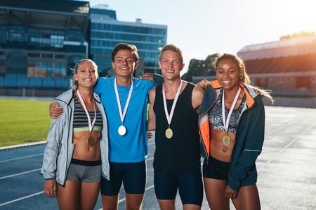 Groep atleten met medailles .Twee jonge vrouw en man samen op zoek naar de camera en glimlachen terwijl staande op atletiek renbaan in stadion.