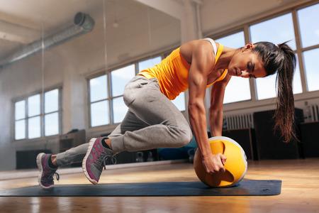 musculoso: Fit hace femenino intenso entrenamiento de la base en el gimnasio. Mujer muscular joven que hace ejercicio básico en la estera de la aptitud en el club de salud.