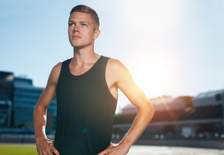 sun track: Young male runner standing with his hands on hips looking away. Determined athlete on race track in athletics stadium with sun flare. Stock Photo