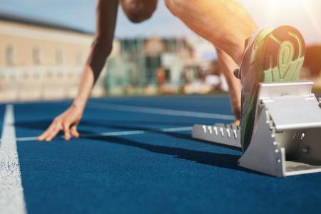 deportistas: Pies en el bloque que comienza listo para empezar la primavera. Concéntrese en las piernas de un atleta a punto de comenzar una carrera en el estadio con la flama del sol.