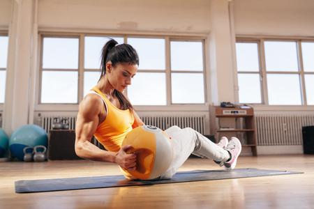 Fitness vrouwelijke model te oefenen met een waterkoker bell gewicht in de sportschool. Fit jonge vrouw doet CrossFit training in health club. Stockfoto