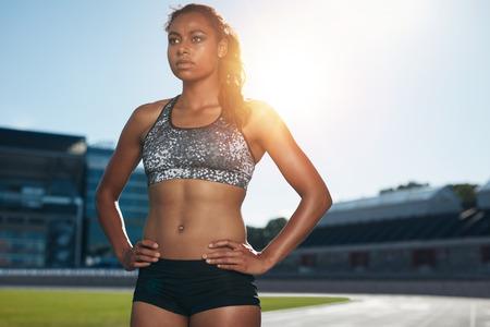 atleta corriendo: Ajuste a la mujer joven de pie con las manos en las caderas mirando a otro lado. Atleta femenina africana se prepara para una carrera en la pista de carreras de atletismo del estadio. Foto de archivo
