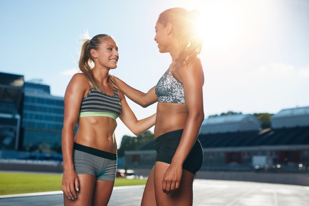 sun track: Two young female runner talking with each other after a run at stadium race track on a bright sunlight. Professional sprinter chatting with sun flare.