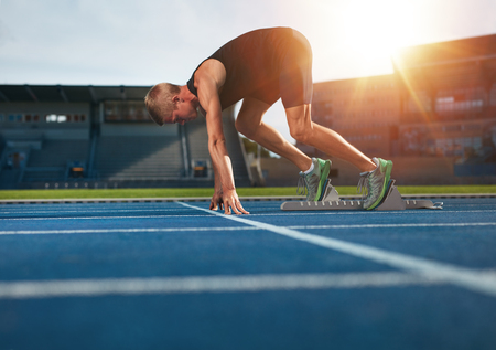 from side: Young man on starting position ready for running. Male athlete in the starting blocks on sports track about to run. Stock Photo