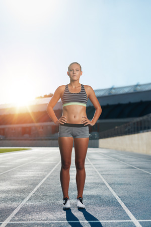 sun track: Full length shot of professional female athlete standing with her hands on hips looking confidently at camera. Runner on race track in athletics stadium with sun flare.