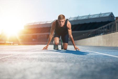 atletismo: Hombre joven atleta en posición lista para comenzar una carrera inicial. Velocista masculino listo para una carrera en pista de carreras que mira la cámara con la flama del sol.