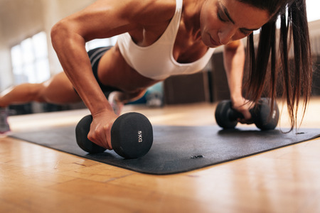 Muscular woman doing push-ups on dumbbells in gym. Powerful female exercising in health club.