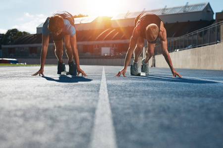 athletics track: Sprinters at starting blocks ready for race . Athletes at starting position on athletics stadium race track with sun flare.
