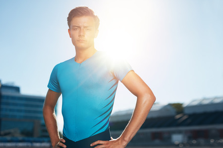 Confident male athlete standing with his hands on hips looking at camera. Runner in athletics stadium with sun flare.