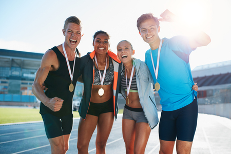 runners: Portrait of young team of athletes enjoying victory. Diverse group of runners with medals celebrating success. Stock Photo