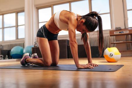 in the back: Tiro de la mujer joven que estira su espalda. Mujer muscular que ejercita en la estera de acondicionamiento f�sico en el gimnasio.