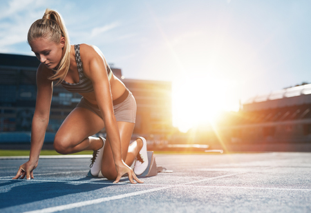 starting position: Young woman athlete at starting position ready to start a race. Female sprinter ready for sports exercise on racetrack with sun flare.