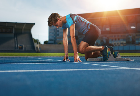 Young athlete at starting position ready to start a race. Male runner ready for sports exercise on racetrack with sun flare.