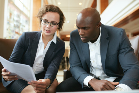 personas hablando: Dos socios de negocios sentados juntos y discutir los documentos del contrato. Los ejecutivos de negocios que van a través de documentos en el vestíbulo.