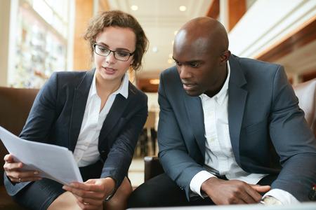 Två affärspartners sitta tillsammans och diskutera förfrågningsunderlaget. Företagsledare går igenom papper i lobbyn. Stockfoto