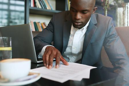 contrato de trabajo: Hombre de negocios en un café leyendo un documento contractual. Ejecutivo de negocios sentado en el café de trabajo.