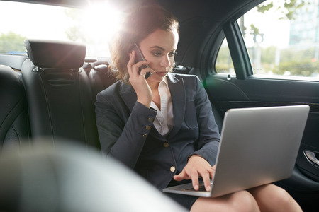 Young businesswoman talking on cell phone sitting in back seat of car. Female CEO using laptop and answering phone call while travelling to office in a car.