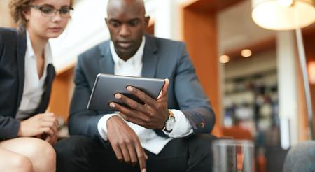 dos personas platicando: Disparo de empresarios que se sientan juntos mirando tableta digital. Enfoque en la tablilla digital en la mano del hombre.