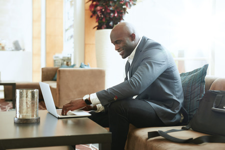 using a computer: Happy businessman using laptop in hotel lobby. African business executive sitting on couch at hotel lobby working on his laptop and smiling. Stock Photo