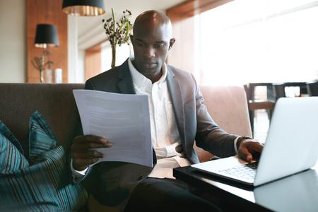 personas leyendo: Imagen de hombre de negocios joven sentado en un establecimiento de leer un documento mientras se trabaja en la computadora portátil. Preparándose para una reunión.