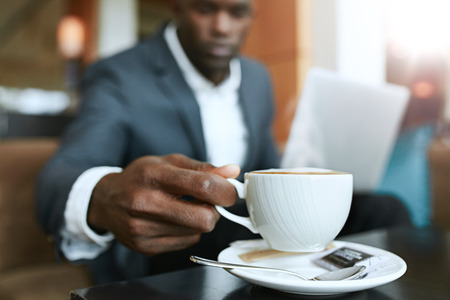 business lifestyle: Close up shot of young man s hand picking up cup of coffee. Businessman sitting at hotel lobby drinking coffee. Stock Photo