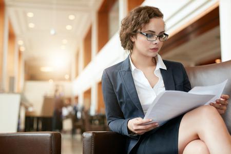 Portret van zakenvrouw lezen document. Vrouwelijke professional in de lobby van het hotel onderzoeken papieren. Stockfoto