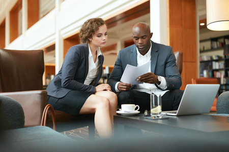 analyzing: Two young business people with papers meeting in hotel lobby. African businessman and caucasian business woman sitting together at a cafe reading contract documents. Stock Photo
