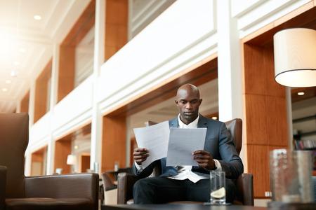administrador de empresas: Retrato de joven empresario ocupado sentado en el lobby del hotel va a través de documentos. Ejecutivos de negocios papeles del contrato de lectura africanos. Foto de archivo