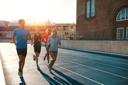 corriendo: Corredores profesionales que se ejecutan en una pista de carreras. Atletas multirraciales que practican en pista de carreras en el estadio en un día soleado brillante. Foto de archivo