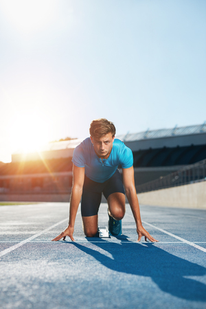 Vertical shot of young male runner taking ready to start position facing the camera. Sprinting with determination. Athlete in starting blocks with sun flare.