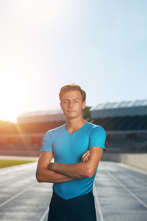 sun track: Professional male track athlete standing with his arms crossed looking at camera. Runner standing in lane at the athletics track in a outdoor athletics stadium with sun flare. Stock Photo