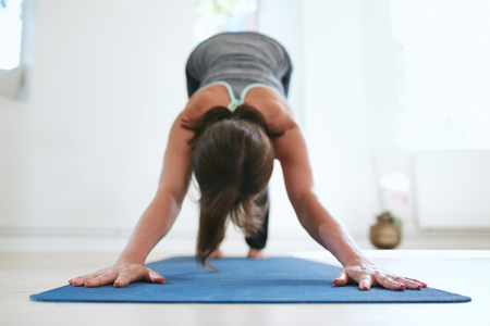 downward: Portrait of woman practicing downward dog pose on yoga mat.  Fitness female in Adho Mukha Svanasana pose. Stock Photo