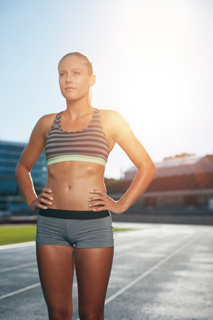sun track: Female runner standing with her hands on hips looking away. Determined woman athlete on race track in athletics stadium with sun flare.