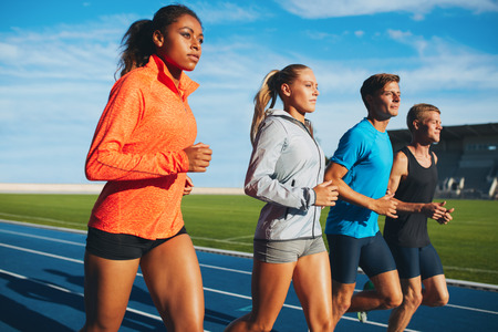 sports venue: Group of diverse sports person practicing running in stadium. Male and female athletes running together on racetrack.