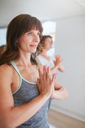 manos unidas: Mujeres que hacen ejercicios de yoga en clase, de pie en actitud del árbol, Vrikshasana con gesto namaste buscando camino sonriendo.