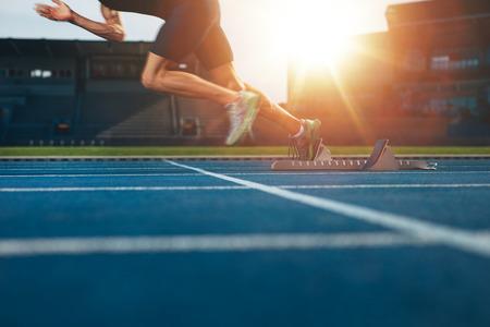 leuchtend: Athlet auf athletische Rennstrecke läuft. Low Abschnitt Schuss von männlichen Läufer ab den Sprint von der Startlinie mit hellen Sonnenlicht.