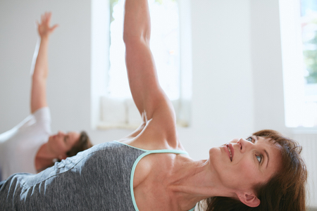 chandrasana: Portrait of a fit mature woman performing a yoga routine at gym. Bending over and looking away with her arms outstretched. Ardha Chandrasana, half Moon pose. Stock Photo