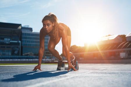 razas de personas: Atleta femenina Confiados en la posición inicial listo para correr. Mujer joven a punto de comenzar una carrera de velocidad que mira lejos con la luz del sol por detrás.