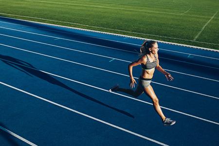 and athlete: Mujer joven que se ejecutan en pista de carreras durante la sesi�n de entrenamiento. Corredor femenino practicando en la pista de atletismo carrera.