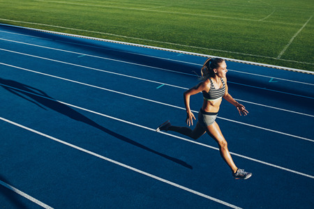 Young woman running on racetrack during training session. Female runner practicing on athletics race track.