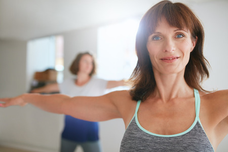 woman warrior: Two women doing stretching and yoga workout at gym. Female trainer with her student in background during physical training session.