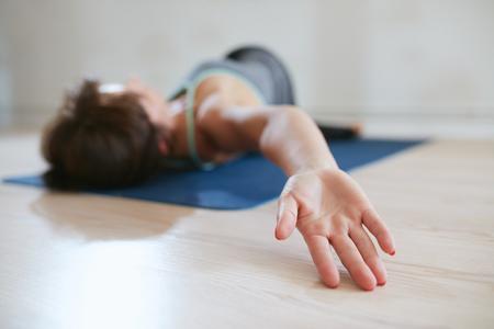 운동 매트에 스트레칭 여자 초점을 손에. 그녀의 시체를 왜곡하는 바닥에 누워 여자입니다.