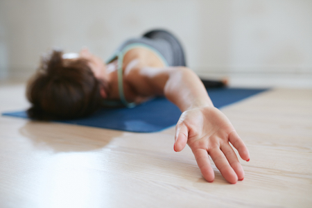 Woman stretching on an exercise mat, focus on hand. Woman lying on floor twisting her body. Stock Photo