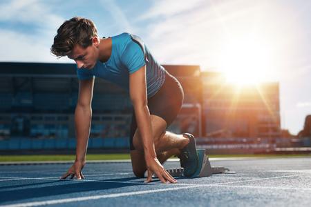 Jonge mannelijke atleet op startblok op renbaan. Jonge man in uitgangspositie voor het rijden op spoor sporten. Sprinter op het punt om een race te beginnen bij stadion met zon flare.