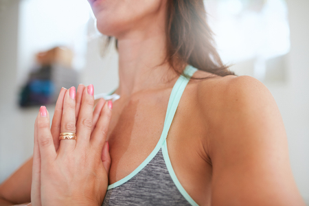 Close up image of woman practicing yoga with her hands joined. Focus on hands. Fitness female meditating in gym.